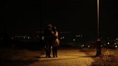 Two lovers, go hug, a walk, in the middle of the night in an alley lit by light Stock Footage