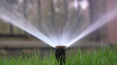 Sprinkler irrigation plant in the garden. The grass is green and beautiful  Stock Footage