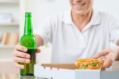 Adult man eating pizza - stock photo