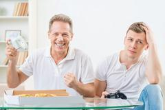 Father and adult son playing video games Stock Photos