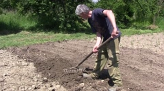 Gardener digging the ground. After the soil is dug, the gardener uses a rake 1 Stock Footage