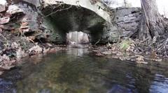 Dried leaves flowing water of a rivulet, passing under an old brick footbridge 1 - stock footage
