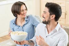 Vivacious couple watching TV - stock photo