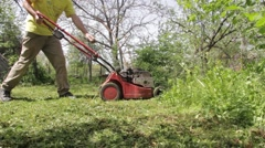 Gardener dressed in long pants, shirt and shoes push lawn mower through tall  Stock Footage