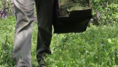 Gardener carrying a basket full of grass clippings after trimming a portion 1 Stock Footage