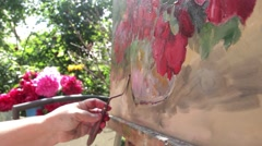 Hand of a painter with a palette knife She paints peonies vase is on the table  Stock Footage