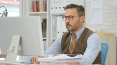Middle-aged businessman with eyeglasses in office Stock Footage