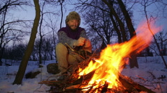 Bearded man warming his hands by the fire in winter. Stock Footage