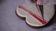 A confectioner decorates cookies in the form of heart Stock Footage