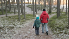 Mother and her little daughter walking through a snowy forrest - stock footage