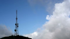 Radio communication antenna towers, mountain peak, clouds sky - stock footage