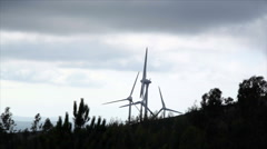 Spinning wind turbine generators in forest mountain Stock Footage