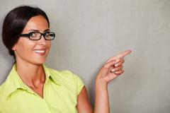 Stock Photo of Female with glasses pointing to her left and smiling with toothy smile while