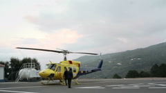Pilots secure yellow helicopter chopper, pan left, Monchique helipad, Portugal Stock Footage