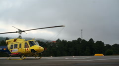 Yellow rescue helicopter chopper, pan left, Monchique helipad, Portugal Stock Footage