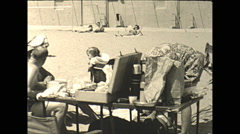 Vintage 16mm film, 1945 USA, family at the beach, toddler in playpen Stock Footage