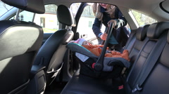 Mother place baby safety chair on back car seat and fasten. 4K Stock Footage