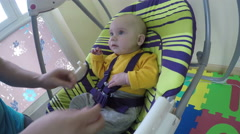 Father man put newborn baby in swing and clip safety belt. 4K Stock Footage