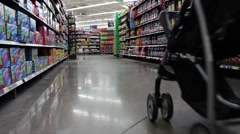 dad pushing baby stroller down walmart aisle - stock footage
