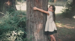 Little girl hugging a tree Stock Footage