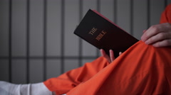 Low angle shot of an inmate reading a bible in prison Stock Footage