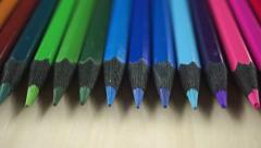 Sharpened color pencils on light wooden table, dolly shot - stock footage