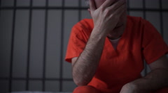 Scene of a depressed inmate crying in prison - stock footage