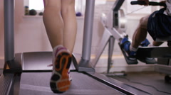 4K Low angle view, the feet of a woman running on a treadmill at the gym - stock footage