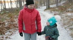 Happy mother and her daughter walking through a snowy forrest. Steadicam shot. - stock footage