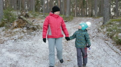 Mother and her little daughter walking through a snowy forrest Stock Footage