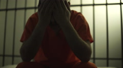 Backlit scene of a depressed inmate in prison - stock footage