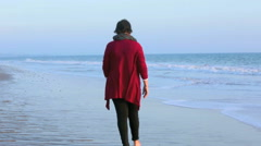 woman walking along the beach at sunset - stock footage