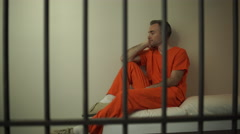 A regretful inmate sitting on bed in prison - stock footage