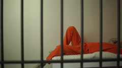 A suicidal inmate in prison laying on bed - stock footage