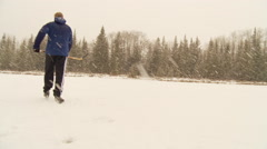 Winter in Banff, walking on river with skates to play hockey in snowstorm Stock Footage