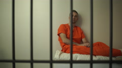 Pensive inmate sits on bed in prison - stock footage