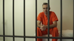 Somber inmate sits on bed in prison - stock footage