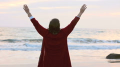 Woman walking along the beach at sunset and stretching her arms Stock Footage