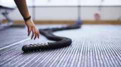 Hands of an unseen woman picking up battle ropes and exercising in the gym Stock Footage