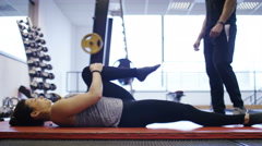 Young flexible woman stretching on a floor mat in the gym as her trainer encoura Stock Footage