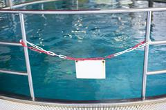 White sign in front of a swimming pool Stock Photos