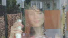 Young woman is cleaning a window and enjoys it Stock Footage