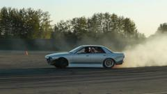Grey car drifting around corner at drift racing event on closed course. - stock footage