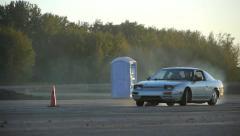 Grey car drifts around corner with pylon stuck underneath it. Stock Footage