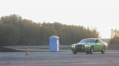 Stock Video Footage of Green dodge challenger cruises on closed course at sunset.