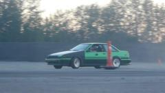 Green/Black car drifting around corner on drift racing track - stock footage