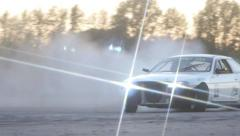 White car drifts around corner on race track at dusk. Stock Footage