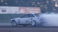 White car burns rubber leaving behind smoke trail on race track. - stock footage