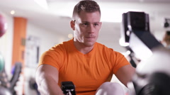 4K Muscular man with prosthetic leg working out on rowing machine at the gym Stock Footage