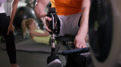 4K Man with prosthetic leg working out at the gym with personal trainer Arkistovideo